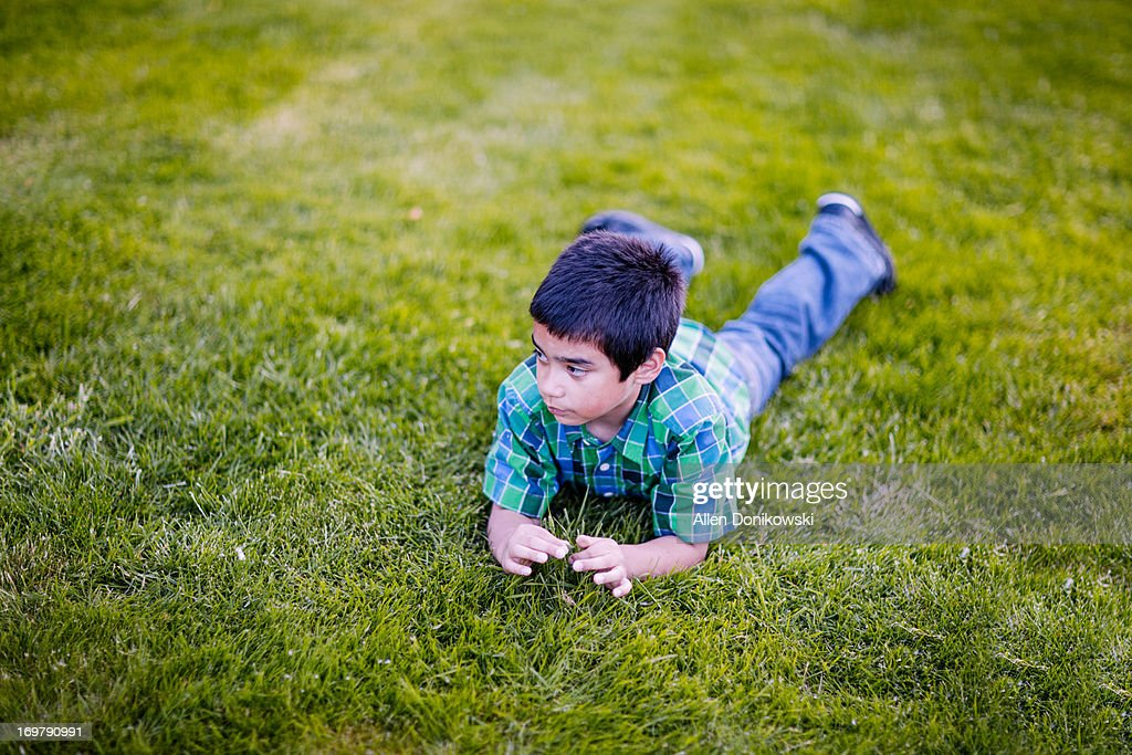 thinking boy laying in grass holding grass : Stock Photo