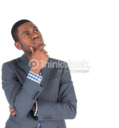 Thinking Businessman Standing With Hand On Chin Stock Photo Thinkstock