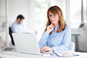 Portrait of attractive professional woman using laptop while working on business report in office.