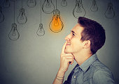 Thinking man looking up with light idea bulb above head isolated on gray wall background