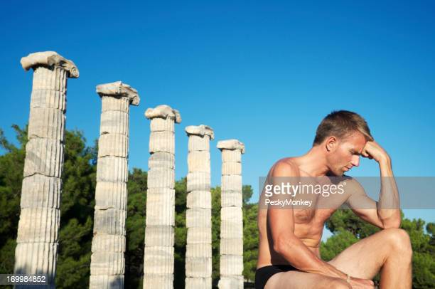 Thinking Man Sits Next to Row of Ancient Columns