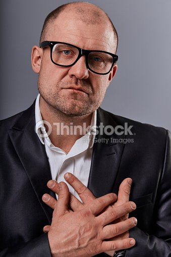 Thinking sad bald business man holding the chest two hands with serious face in eyeglasses in suit on grey background. Closeup : Stock Photo