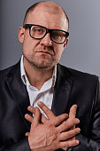 Thinking sad bald business man holding the chest two hands with serious face in eyeglasses in suit on grey background. Closeup portrait