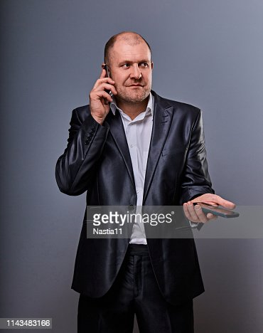Thinking stressed angry doubt business man talking on mobile phone very emotional in office suit on grey background. Closeup : Stock Photo