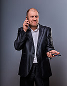 Thinking stressed angry doubt business man talking on mobile phone very emotional in office suit on grey background. Closeup portrait