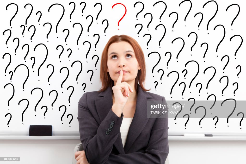 thinking woman in front of question marks written whiteboard