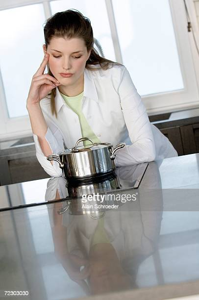 Thinking woman watching over saucepan on vitroceramic hob