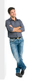 Happy smiling young man leaning against white wall with dreaming and pensive expression, copy space on the right.