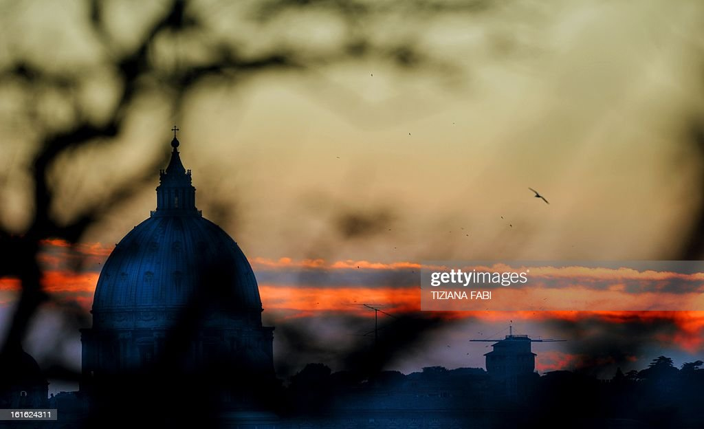 Thios picture shows the sunset over St peter's basilica on February 13, 2013 at the Vatican. Pope Benedict XVI made his first public appearance on Wednesday since his shock resignation announcement, asking thousands of cheering pilgrims at the Vatican to 'keep praying for me'. AFP PHOTO / TIZIANA FABI