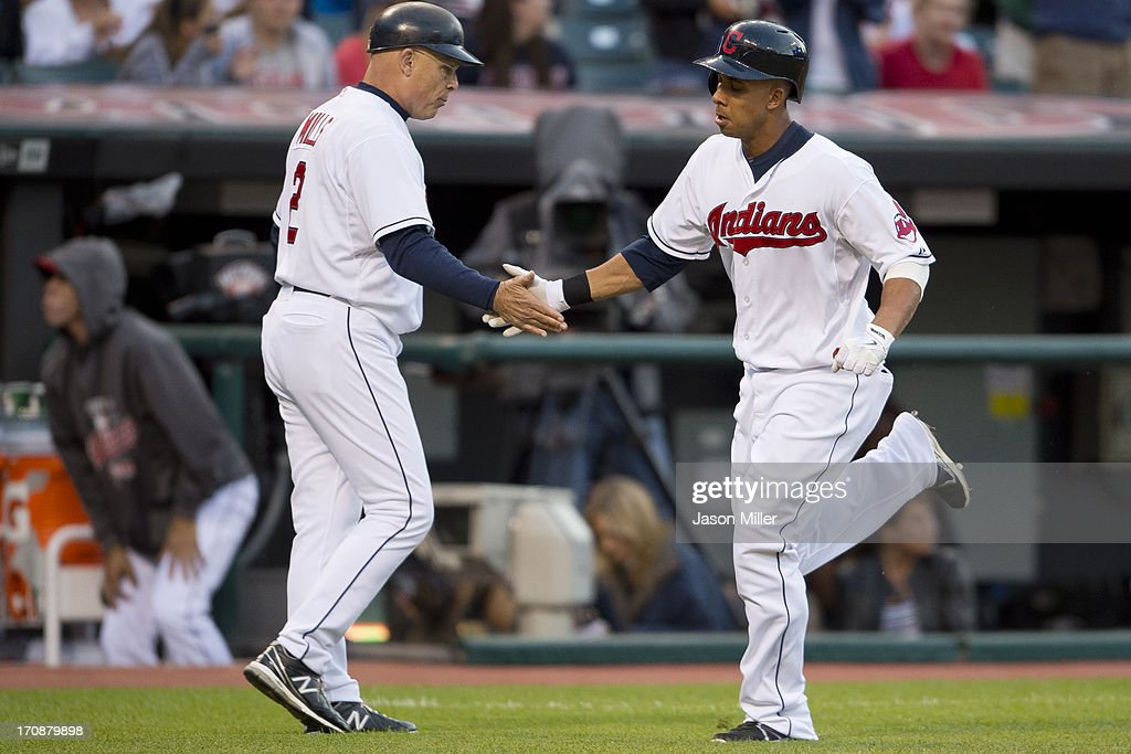 Third base coach Brad Mills #2 celebrates with Michael Brantley #23 of the Cleveland Indians after Brantley hit a solo home run during the fifth inning against the Kansas City Royals at Progressive Field on June 19, 2013 in Cleveland, Ohio.
