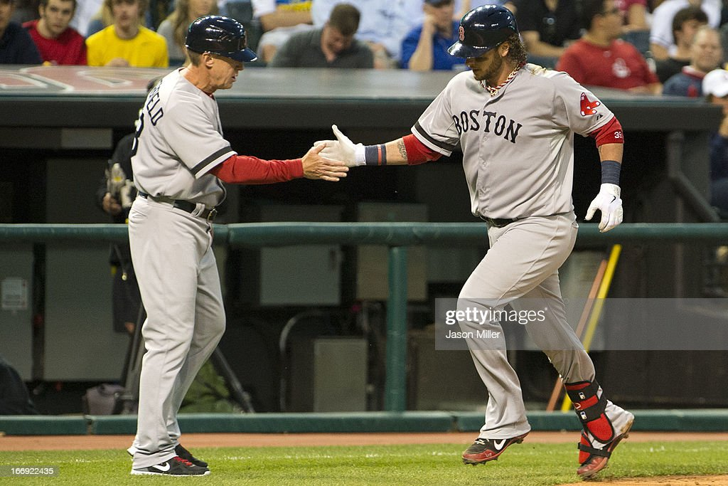 Third base coach Brian Butterfield #13 congratulates Jarrod Saltalamacchia #39 of the Boston Red Sox after Saltalamacchia hit a solo home run in the fourth inning against the Cleveland Indians at Progressive Field on April 18, 2013 in Cleveland, Ohio.