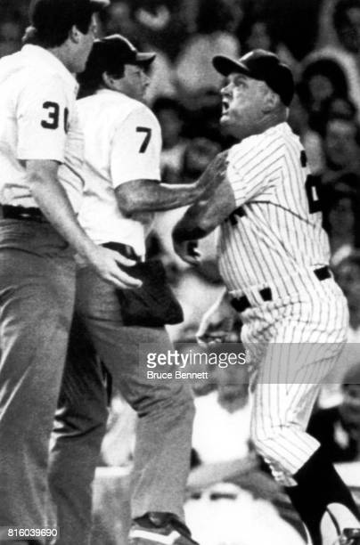 Third base coach Don Zimmer of the New York Yankees is held back by home plate umpire Dave Phillips as Zimmer tries to get at Tim Welke after Welke...