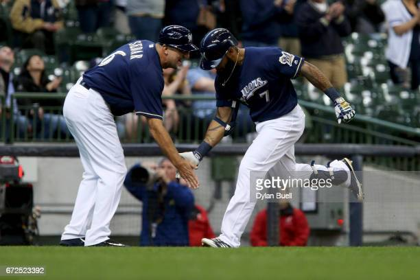 Third base coach Ed Sedar of the Milwaukee Brewers congratulates Eric Thames after hitting a home run in the first inning against the Cincinnati Reds...