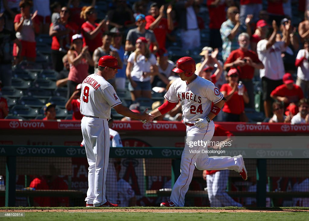 Third base coach Gary DiSarcina #9 of the Los Angeles Angels of Anaheim congratulates C.J. Cron #24 as Cron rounds third base on his way to home plate after hitting a solo homerun in the seventh inning against the Houston Astros during the MLB game at Angel Stadium of Anaheim on September 13, 2015 in Anaheim, California.