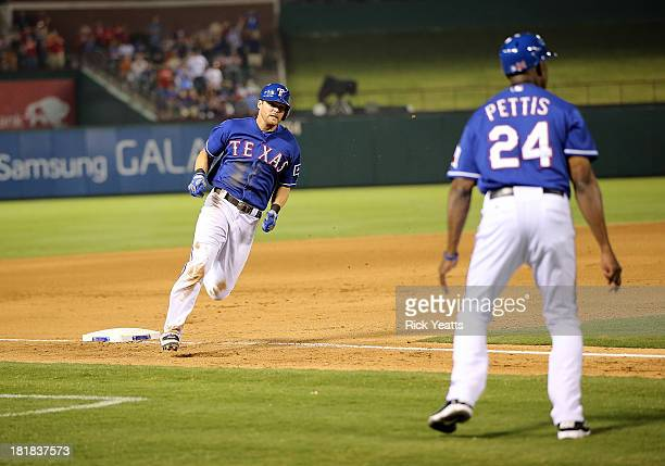 Third base coach Gary Pettis looks on as Craig Gentry of the Texas Rangers rounds third base to score in the third inning against the Houston Astros...