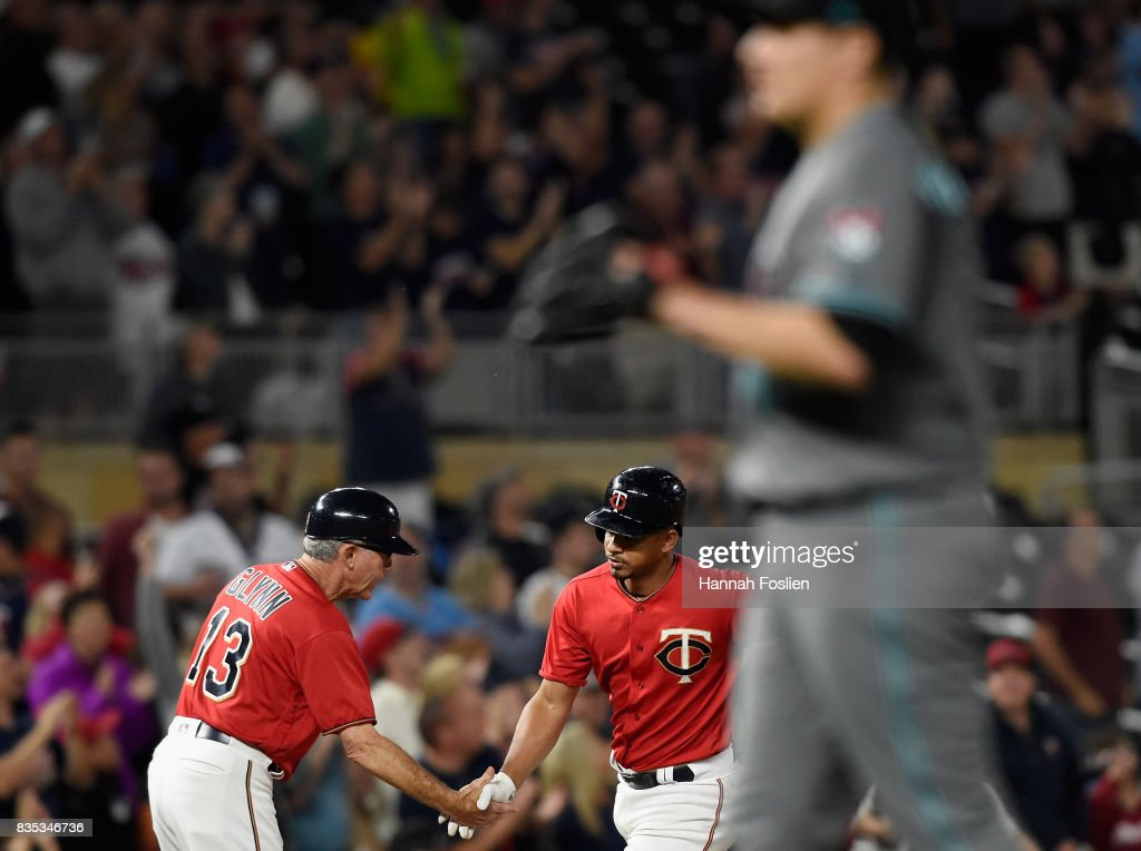Third base coach Gene Glynn #13 of the Minnesota Twins congratulates Eduardo Escobar #5 on a two-run home run as David Hernandez #47 of the Arizona Diamondbacks looks on during the seventh inning of the game on August 18, 2017 at Target Field in Minneapolis, Minnesota. The Twins defeated the Diamondbacks 10-3.