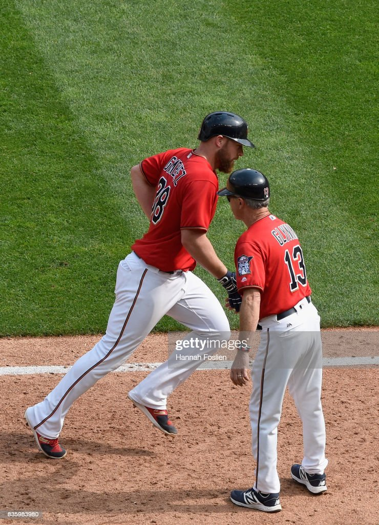 Third base coach Gene Glynn #13 of the Minnesota Twins congratulates Chris Gimenez #38 on a solo home run against the Arizona Diamondbacks during the fifth inning of the game on August 20, 2017 at Target Field in Minneapolis, Minnesota. The Twins defeated the Diamondbacks 12-5.