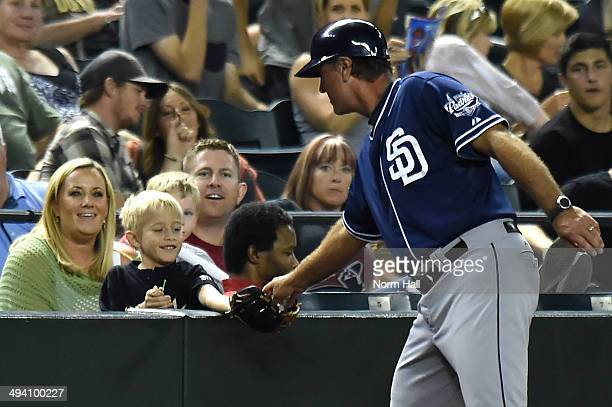 Third Base Coach Glenn Hoffman of the San Diego Padres gives a foul ball to a young fan during a game against the Arizona Diamondbacks at Chase Field...