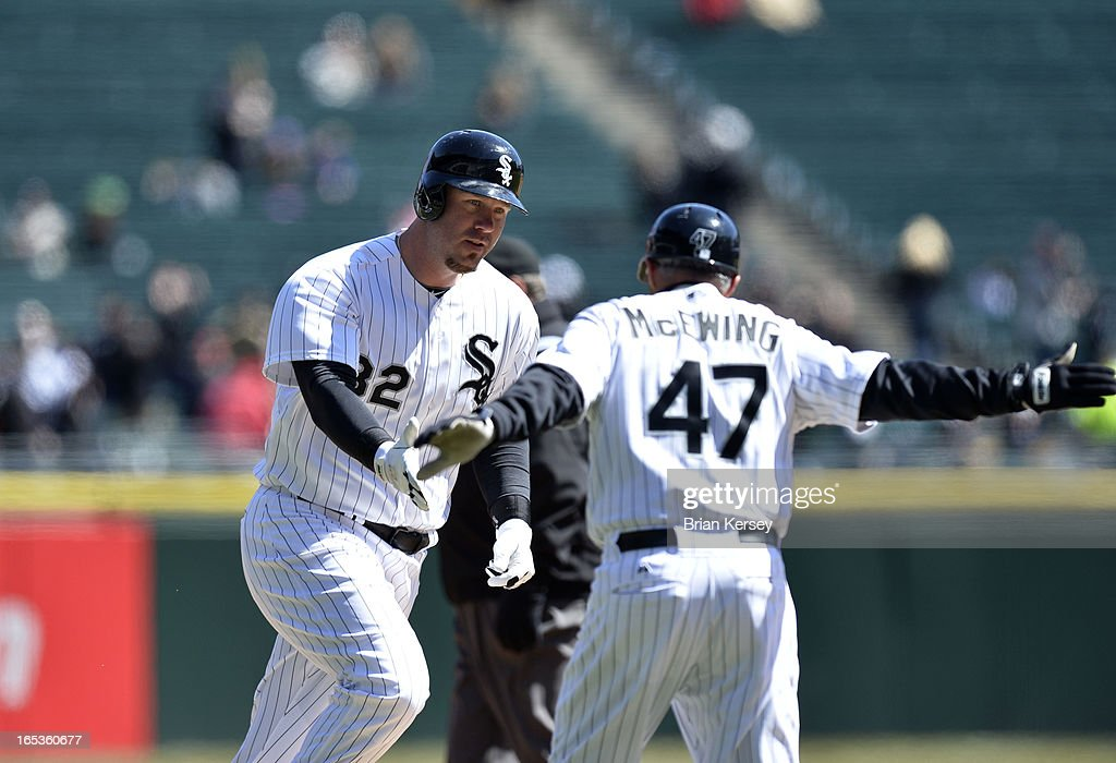 Third base coach <a gi-track='captionPersonalityLinkClicked' href=/galleries/search?phrase=Joe+McEwing&family=editorial&specificpeople=211298 ng-click='$event.stopPropagation()'>Joe McEwing</a> #47 of the Chicago White Sox high-fives <a gi-track='captionPersonalityLinkClicked' href=/galleries/search?phrase=Adam+Dunn&family=editorial&specificpeople=213505 ng-click='$event.stopPropagation()'>Adam Dunn</a> #32 of the White Sox as he rounds the bases after hitting a solo home run during the second inning against the Kansas City Royals on April 3, 2012 at U.S. Cellular Field in Chicago, Illinois.