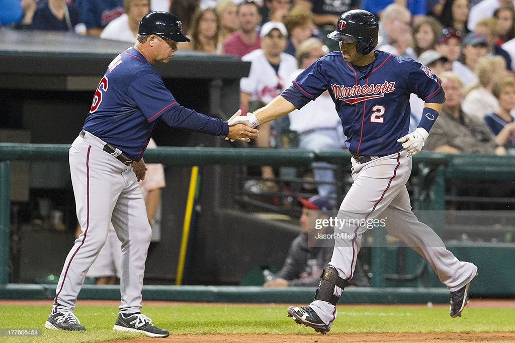 Third base coach Joe Vavra #46 congratulates <a gi-track='captionPersonalityLinkClicked' href=/galleries/search?phrase=Brian+Dozier&family=editorial&specificpeople=7553002 ng-click='$event.stopPropagation()'>Brian Dozier</a> #2 of the Minnesota Twins as he round the bases after hitting a solo home run during the eighth inning against the Cleveland Indians at Progressive Field on August 24, 2013 in Cleveland, Ohio.