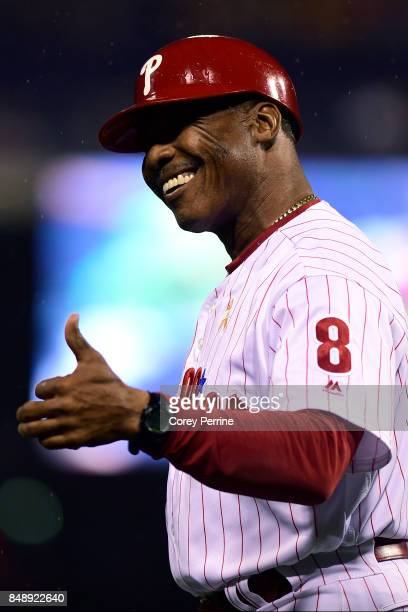 Third base coach Juan Samuel of the Philadelphia Phillies gives a thumbs up to a fan during the second inning at Citizens Bank Park on September 16...