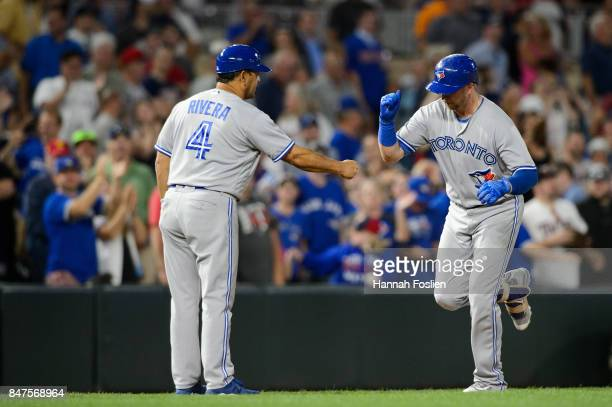 Third base coach Luis Rivera of the Toronto Blue Jays congratulates Justin Smoak on a solo home run against the Minnesota Twins as he runs the bases...