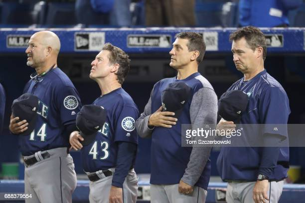 Third base coach Manny Acta of the Seattle Mariners and first base coach Casey Candaele and bench coach Tim Bogar and manager Scott Servais stand...
