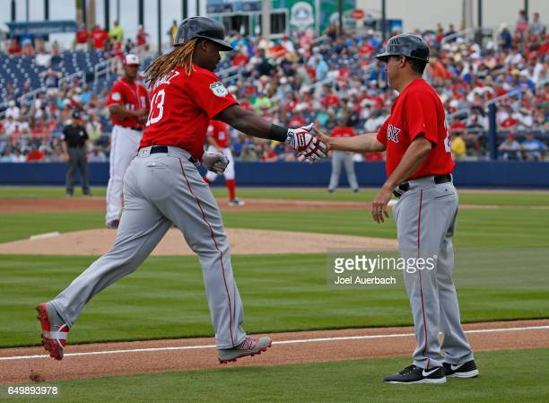 Third base coach Ruben Amaro congratulates Hanley Ramirez of the Boston Red Sox after he hit a home run against the Washington Nationals in the first...