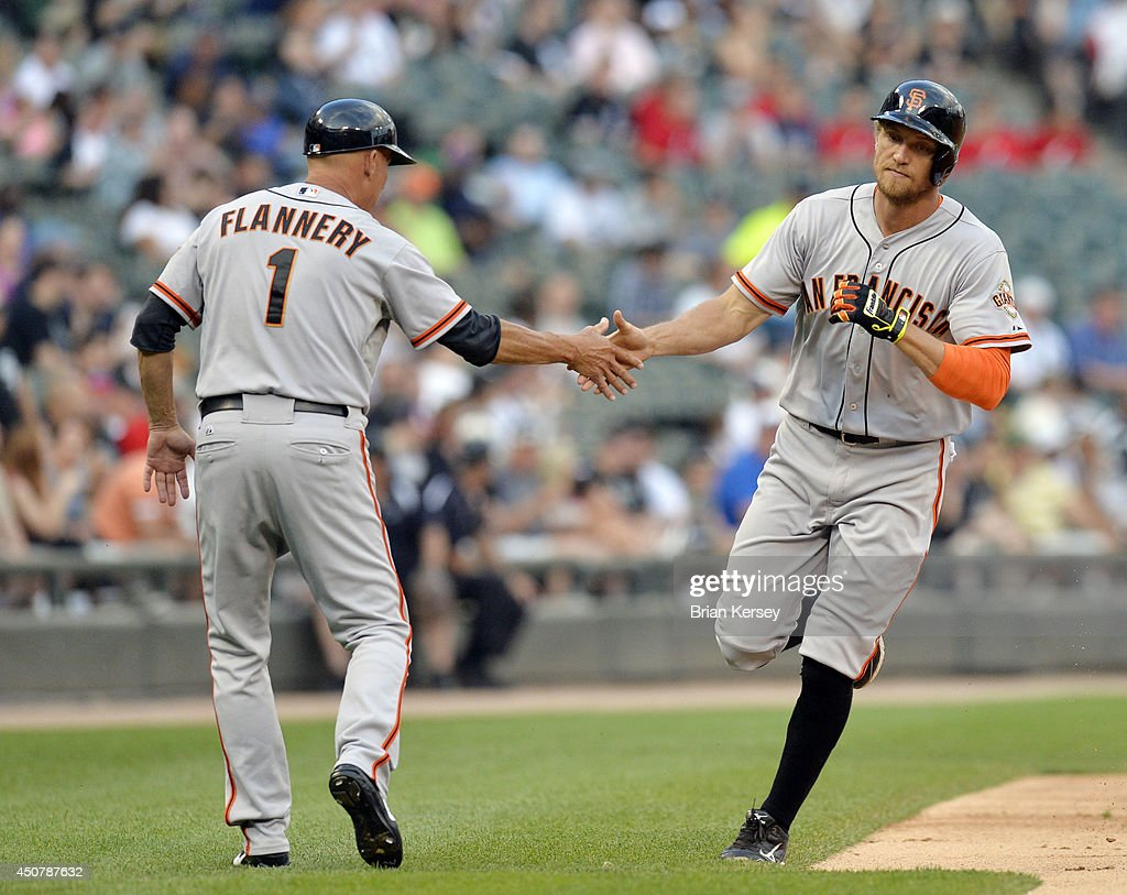 Third base coach Tim Flannery #1 of the San Francisco Giants congratulates Hunter Pence #8 of the San Francisco Giants as he rounds the bases after hitting a solo home run during the first inning against the Chicago White Sox at U.S. Cellular Field on June 17, 2014 in Chicago, Illinois.
