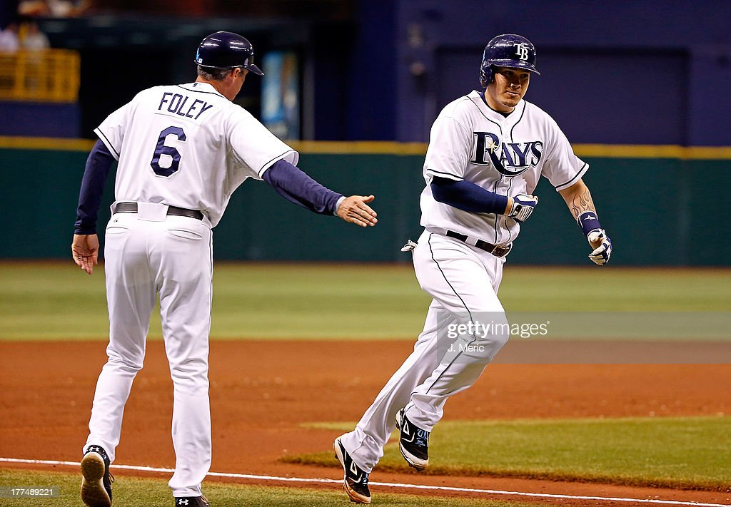 Third base coach Tom Foley #6 of the Tampa Bay Rays congratulates catcher Jose Lobaton #59 after his second inning three run home run against the New York Yankees during the game at Tropicana Field on August 23, 2013 in St. Petersburg, Florida.