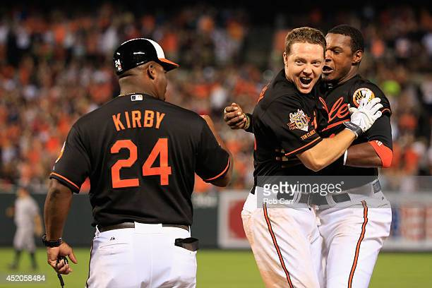 Third base coach Wayne Kirby and Adam Jones of the Baltimore Orioles celebrate with teammate Nick Hundley after Hundley hit the game winning single...