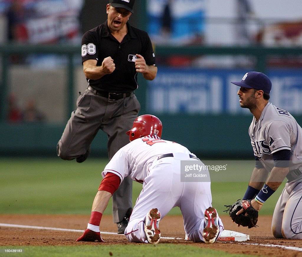 Third base umpire Chris Guccione #68 signals <a gi-track='captionPersonalityLinkClicked' href=/galleries/search?phrase=Mike+Trout&family=editorial&specificpeople=7091306 ng-click='$event.stopPropagation()'>Mike Trout</a> #27 of the Los Angeles Angels of Anaheim out, tagged by <a gi-track='captionPersonalityLinkClicked' href=/galleries/search?phrase=Sean+Rodriguez&family=editorial&specificpeople=4171805 ng-click='$event.stopPropagation()'>Sean Rodriguez</a> #1 of the Tampa Bay Rays, completing an unassisted double play in the first inning at Angel Stadium of Anaheim on August 17, 2012 in Anaheim, California.