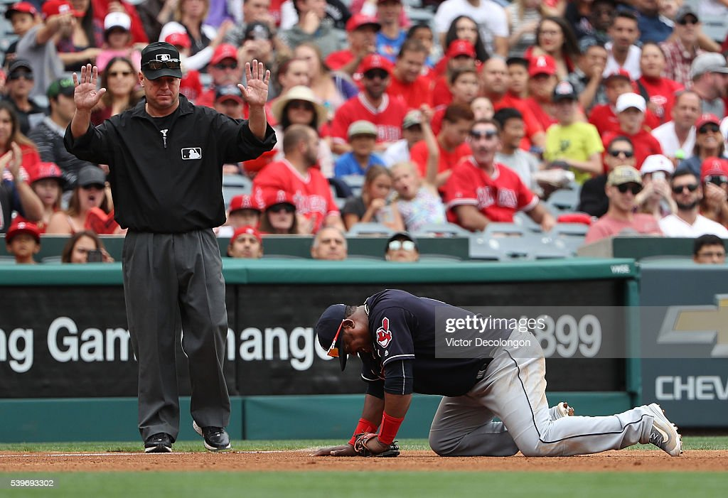 Third base umpire Rob Drake calls time out as Juan Uribe of the Cleveland Indians stays down after stopping a ground ball with his body in the fourth...