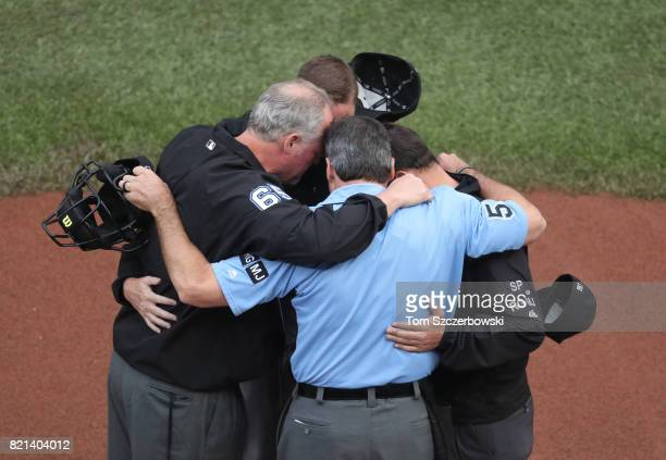 Third base umpire Ted Barrett and second base umpire Chad Whitson and first base umpire Quinn Wolcott and home plate umpire Angel Hernandez huddle in...