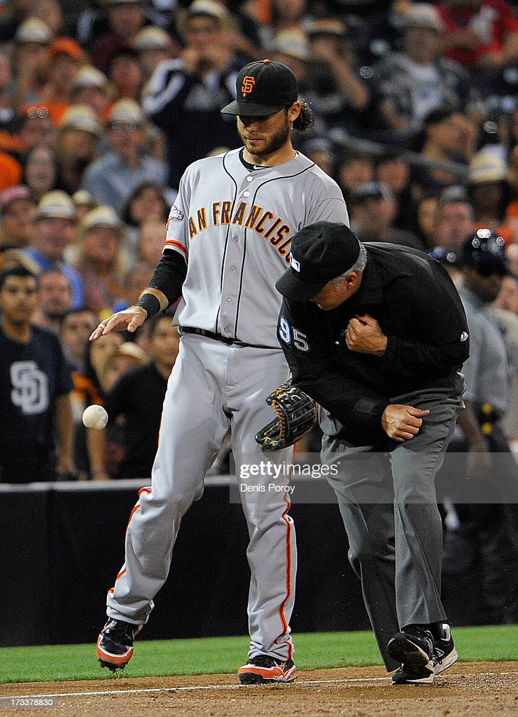 Third base umpire <a gi-track='captionPersonalityLinkClicked' href=/galleries/search?phrase=Tim+Timmons&family=editorial&specificpeople=224662 ng-click='$event.stopPropagation()'>Tim Timmons</a> gets in the way of <a gi-track='captionPersonalityLinkClicked' href=/galleries/search?phrase=Brandon+Crawford&family=editorial&specificpeople=5580312 ng-click='$event.stopPropagation()'>Brandon Crawford</a> #35 of the San Francisco Giants as he goes for a foul ball during the third inning of a baseball game against the San Diego Padres at Petco Park on July 12, 2013 in San Diego, California.