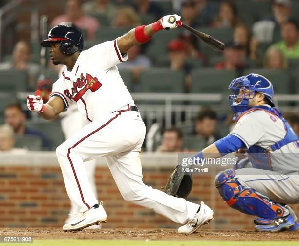Third baseman Adonis Garcia of the Atlanta Braves hits an RBI single in the fourth inning while catcher Travis d'Arnaud of the New York Mets looks on...