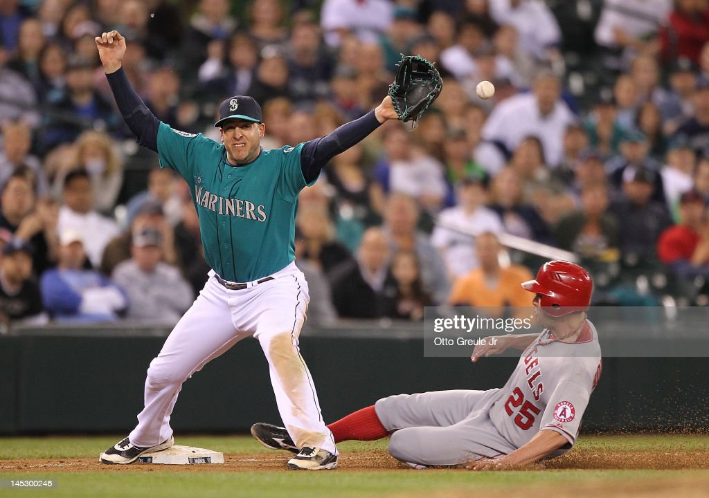 Third baseman <a gi-track='captionPersonalityLinkClicked' href=/galleries/search?phrase=Alex+Liddi&family=editorial&specificpeople=5751736 ng-click='$event.stopPropagation()'>Alex Liddi</a> #16 of the Seattle Mariners can't handle the throw from closing pitcher Brandon League on a force out attempt in the ninth inning as <a gi-track='captionPersonalityLinkClicked' href=/galleries/search?phrase=Peter+Bourjos&family=editorial&specificpeople=4959085 ng-click='$event.stopPropagation()'>Peter Bourjos</a> #25 of the Los Angeles Angels of Anaheim slides in safely at Safeco Field on May 25, 2012 in Seattle, Washington. League was charged with an error on the play.