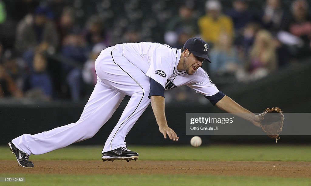 Third baseman <a gi-track='captionPersonalityLinkClicked' href=/galleries/search?phrase=Alex+Liddi&family=editorial&specificpeople=5751736 ng-click='$event.stopPropagation()'>Alex Liddi</a> #16 of the Seattle Mariners dives for a single off the bat of <a gi-track='captionPersonalityLinkClicked' href=/galleries/search?phrase=Brandon+Allen+-+Baseball+Player&family=editorial&specificpeople=2238262 ng-click='$event.stopPropagation()'>Brandon Allen</a> of the Oakland Athletics at Safeco Field on September 27, 2011 in Seattle, Washington.