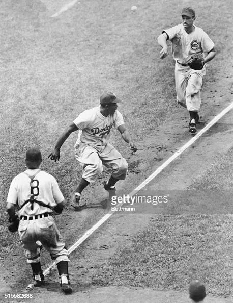 Third baseman Andy Pafko tosses the ball to catcher Rube Walker as the two trap base runner Jackie Robinson between third base and home in a game...