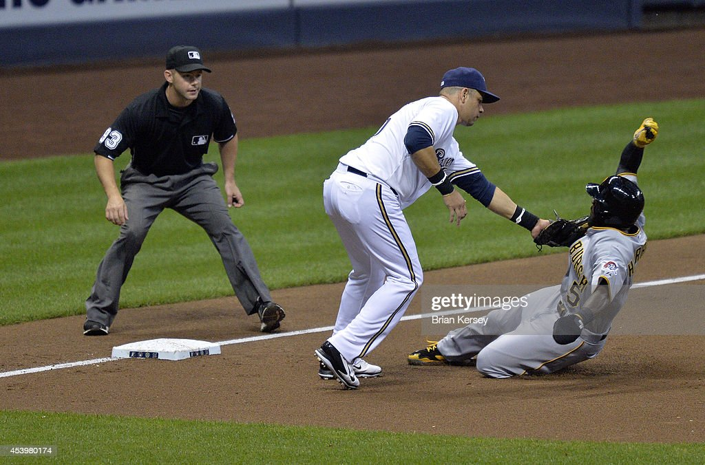 Third baseman Aramis Ramirez #16 of the Milwaukee Brewers (C) tags out Josh Harrison #5 of the Pittsburgh Pirates (R) as he tries to steal third base during the second inning at Miller Park on August 22, 2014 in Milwaukee, Wisconsin. Third base umpire Will Little waits to make the call.