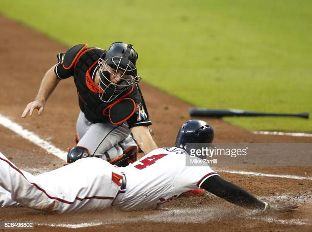 Third baseman Brandon Phillips of the Atlanta Braves slides into home plate to score behind catcher JT Realmuto of the Miami Marlins in the first...