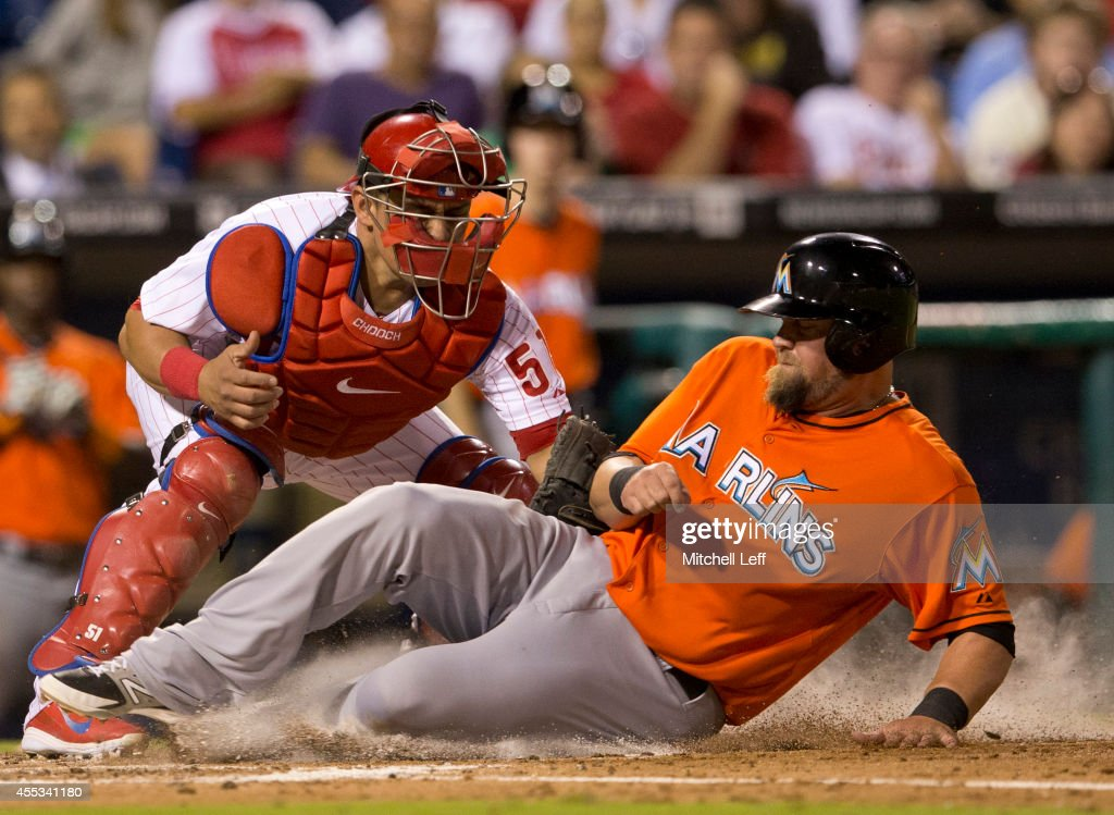 Third baseman Casey McGehee of the Miami Marlins is tagged out at home by catcher Carlos Ruiz of the Philadelphia Phillies in the top of the fourth...