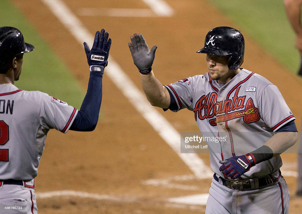 Third baseman Chris Johnson of the Atlanta Braves high fives center fielder BJ Upton after hitting a two run home run in the top of the fourth inning...