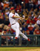 Third Baseman Cody Asche of the Philadelphia Phillies makes a throw to first on a ball hit by Tucker Barnhart of the Cincinnati Reds the seventh...