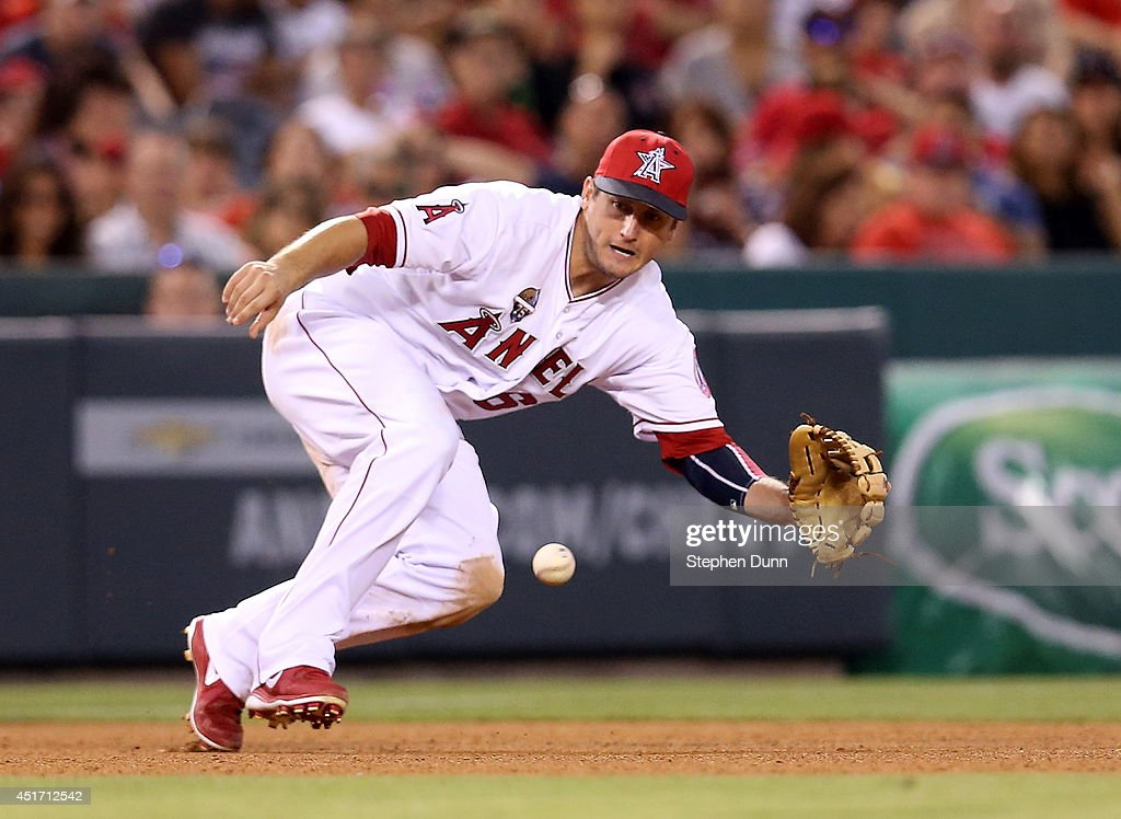 Third baseman <a gi-track='captionPersonalityLinkClicked' href=/galleries/search?phrase=David+Freese+-+Baseball+Player&family=editorial&specificpeople=4948315 ng-click='$event.stopPropagation()'>David Freese</a> #6 of the Los Angeles Angels of Anaheim dives to field a ground ball hit by L.J. Hoes of the Houston Astros for the first out of the seventh inning at Angel Stadium of Anaheim on July 4, 2014 in Anaheim, California.