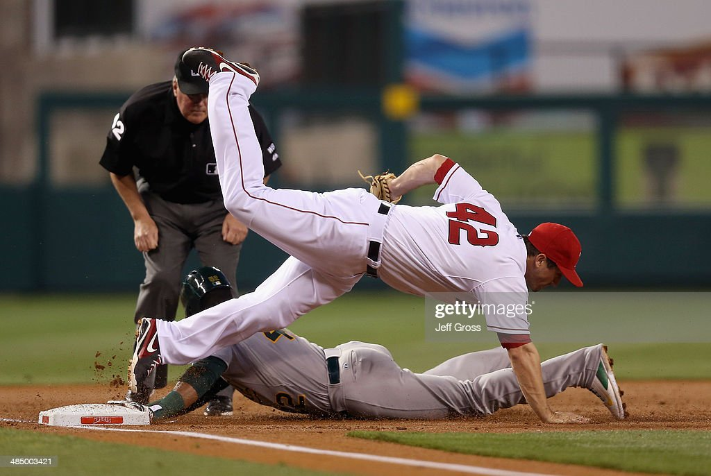 Third baseman <a gi-track='captionPersonalityLinkClicked' href=/galleries/search?phrase=David+Freese+-+Baseball+Player&family=editorial&specificpeople=4948315 ng-click='$event.stopPropagation()'>David Freese</a> of the Los Angeles Angels of Anaheim falls over <a gi-track='captionPersonalityLinkClicked' href=/galleries/search?phrase=Yoenis+Cespedes&family=editorial&specificpeople=8892047 ng-click='$event.stopPropagation()'>Yoenis Cespedes</a> of the Oakland Athletics after tagging him out as he was attempting to advance in the second inning at Angel Stadium of Anaheim on April 15, 2014 in Anaheim, California. All uniformed team members are wearing jersey number 42 in honor of Jackie Robinson Day.