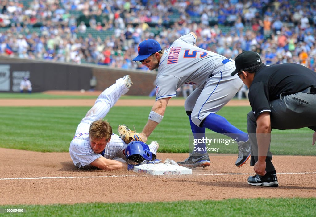 Third baseman <a gi-track='captionPersonalityLinkClicked' href=/galleries/search?phrase=David+Wright+-+Baseball+Player&family=editorial&specificpeople=209172 ng-click='$event.stopPropagation()'>David Wright</a> #5 of the New York Mets (C) tags out <a gi-track='captionPersonalityLinkClicked' href=/galleries/search?phrase=Ryan+Sweeney&family=editorial&specificpeople=711121 ng-click='$event.stopPropagation()'>Ryan Sweeney</a> #6 of the Chicago Cubs at third base as third base umpire Manny Gonzalez (R) looks to make the call during the fourth inning on May 19, 2013 at Wrigley Field in Chicago, Illinois. Sweeney tried to stretch a double into a triple.