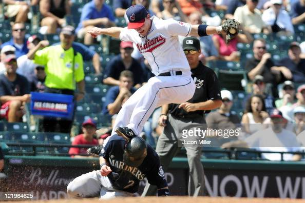 Third baseman Jack Hannahan of the Cleveland Indians lands on Brendan Ryan of the Seattle Mariners after jumping to catch a high throw to third base...