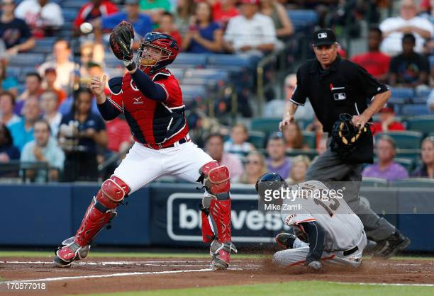 Third baseman Joaquin Arias of the San Francisco Giants slides into home plate before a throw to catcher Brian McCann of the Atlanta Braves while...