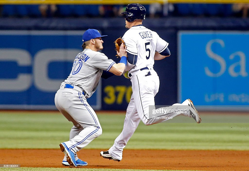 Third baseman <a gi-track='captionPersonalityLinkClicked' href=/galleries/search?phrase=Josh+Donaldson&family=editorial&specificpeople=4959442 ng-click='$event.stopPropagation()'>Josh Donaldson</a> #20 of the Toronto Blue Jays catches Brandon Guyer #5 of the Tampa Bay Rays out in a run down between first base and second base after Guyer attempted to stretch a single into a double during the second inning of a game on April 29, 2016 at Tropicana Field in St. Petersburg, Florida.